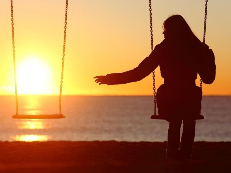 grieving woman alone on a swing by the beach at sunset